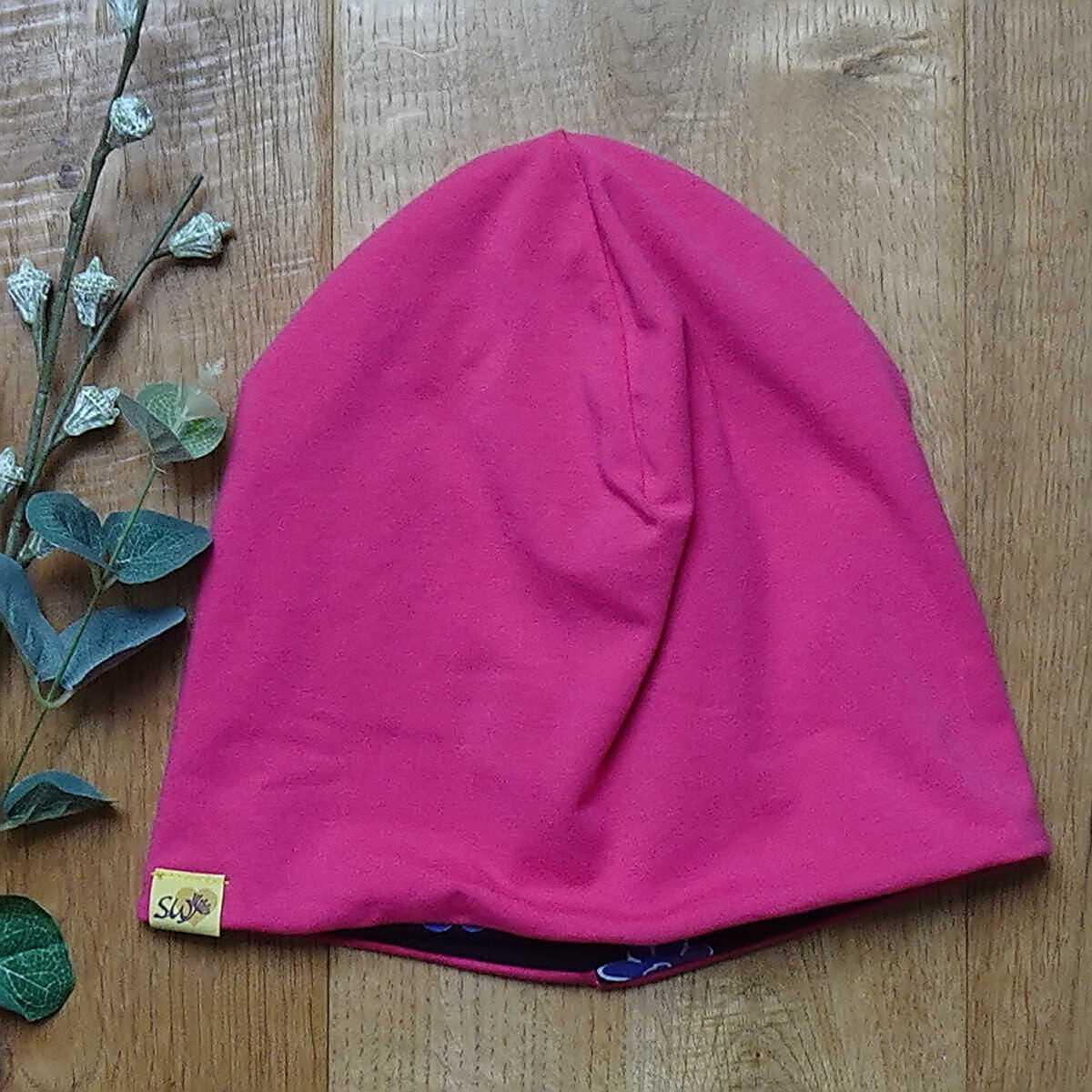 Wende-Beanie mit Muster Blumen auf schwarz Rückseite Pink